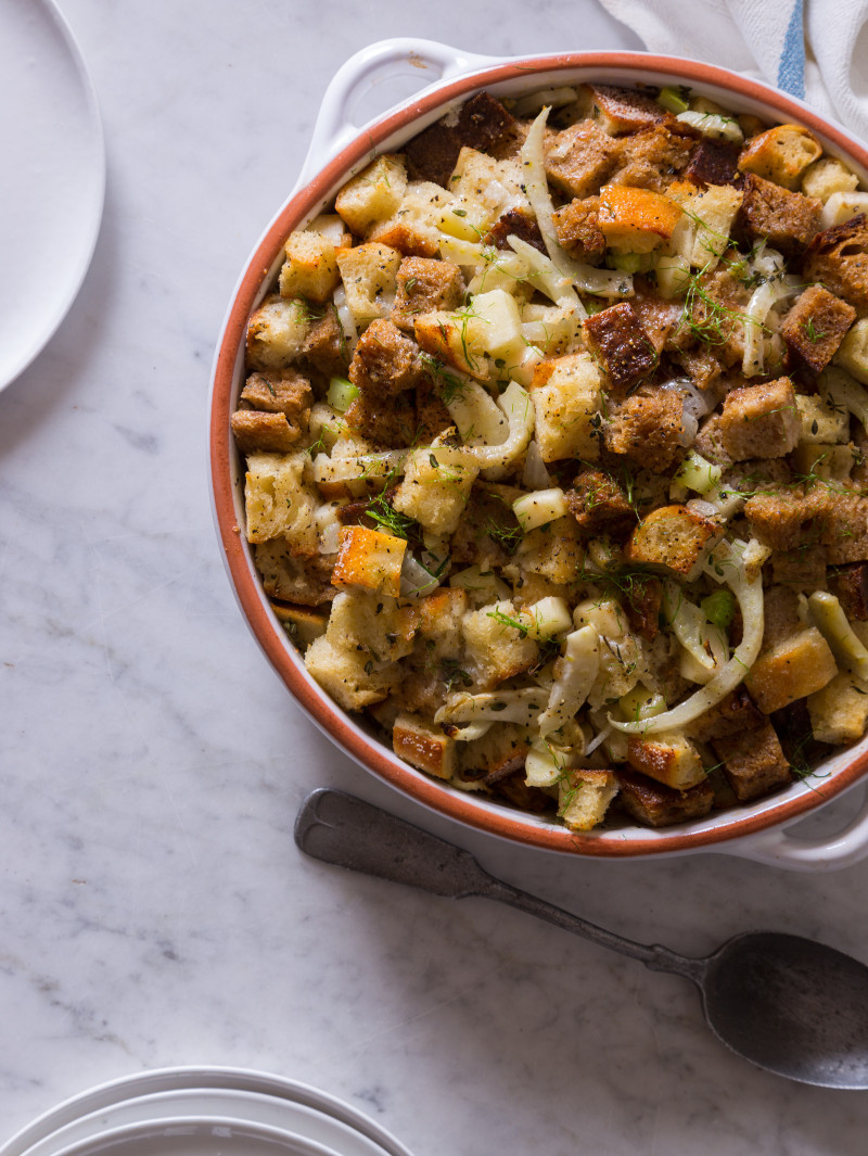 A bowl of apple and fennel stuffing with a spoon.