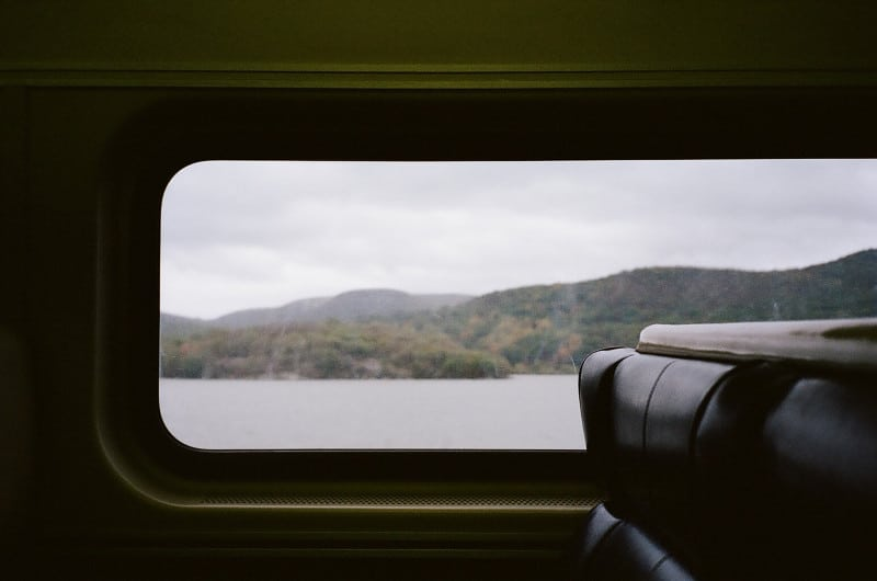A view from a train window of water and mountains.