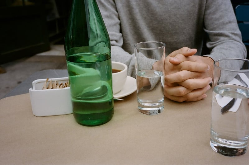 A person sitting at a table with a cup of coffee and a bottle of water.