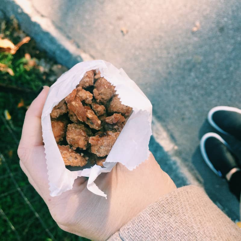 A hand holding a bag of candied cashews.