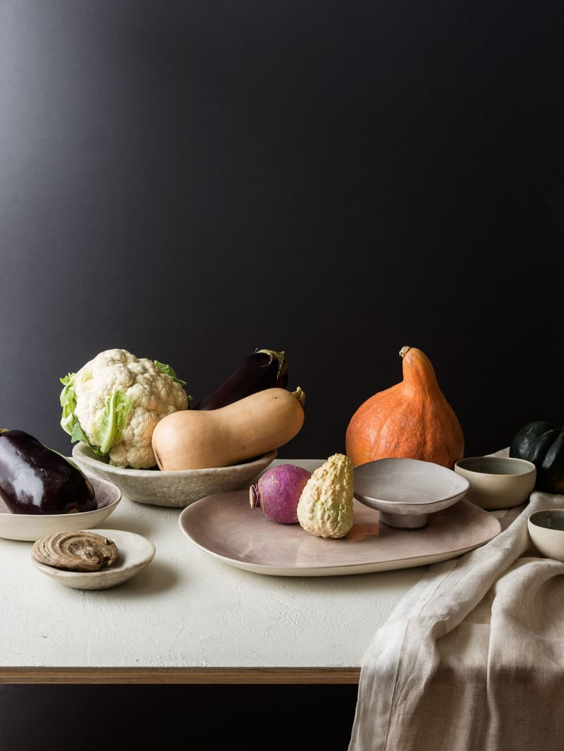 A flowerless Thanksgiving centerpiece made with fruits and vegetables on plates.