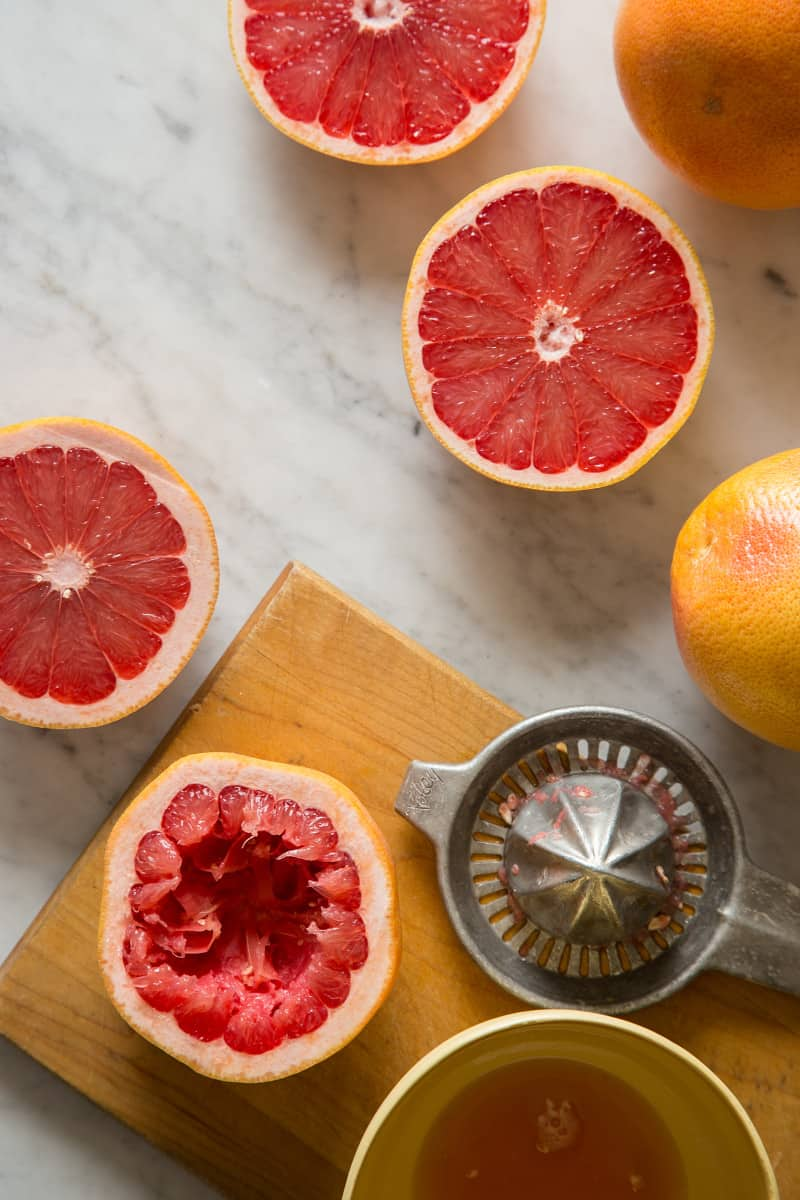 Red grapefruits cut in half, being juiced with a citrus juicer.