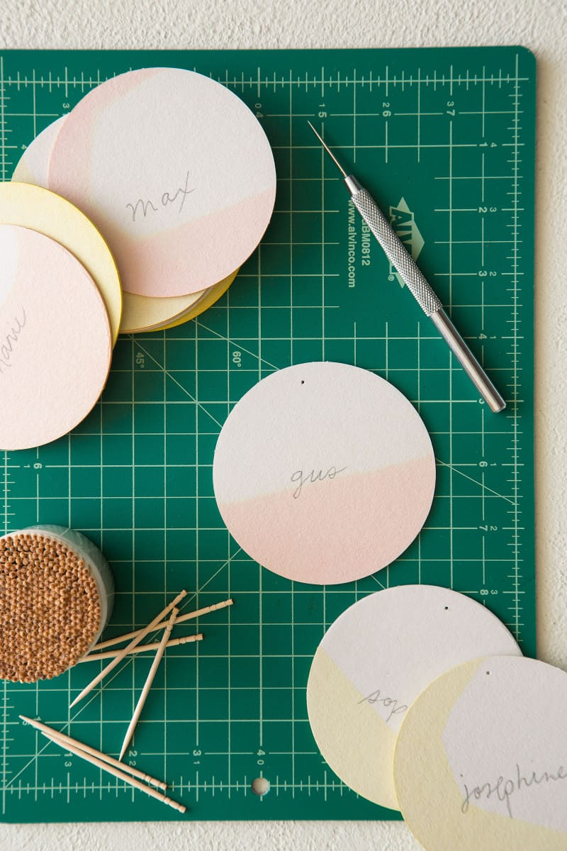DIY dip dye place cards on a cutting mat with tooth picks and and awl.