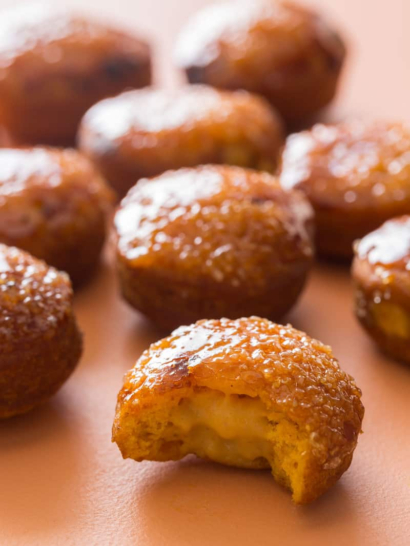 A close up of pumpkin crème brûlée doughnuts with a bite taken out of one.