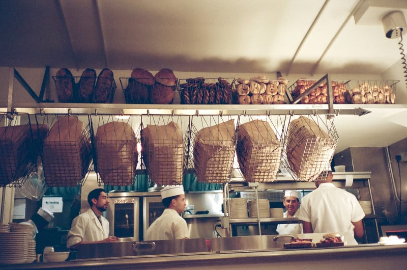 A group of cooks in a kitchen with bagels and bins above.
