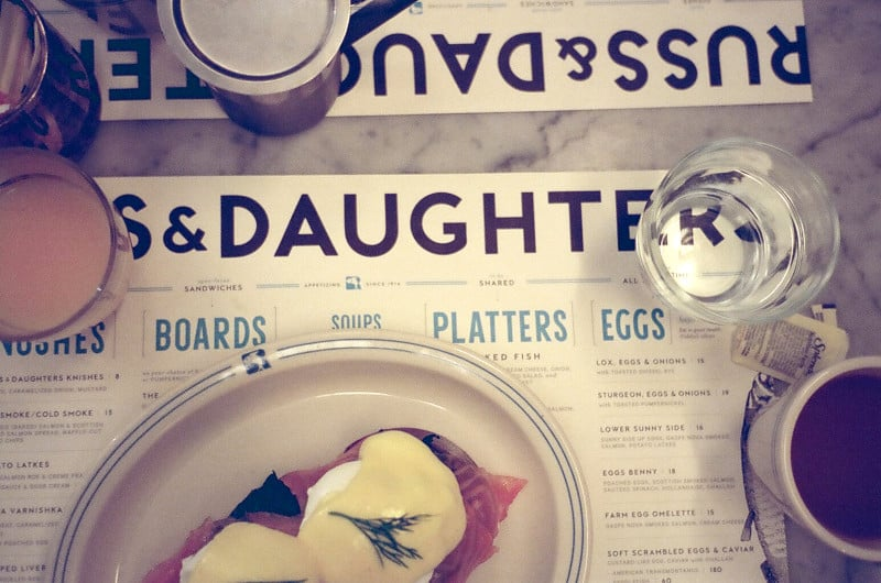 Menus with a plate of salmon benedict and drinks on top.