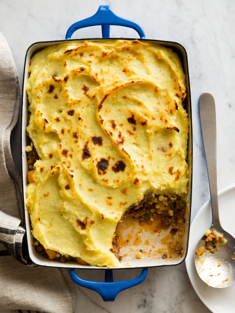 A baking pan of sweet potato shepherd's pie with a portion taken out and a spoon.