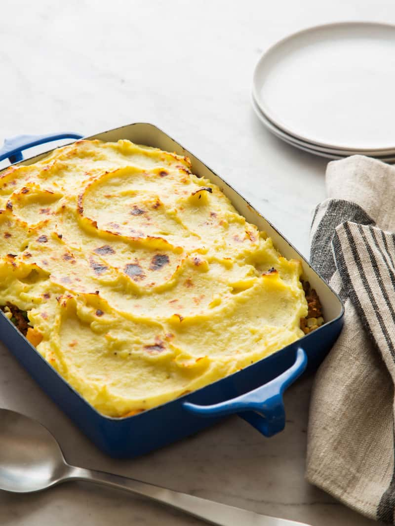 A baking pan of sweet potato shepherd's pie with plates and linens.
