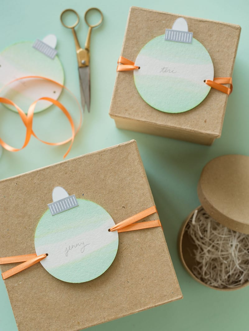 Dip dye ornament gift tags tied onto brown gift boxes with scissors.