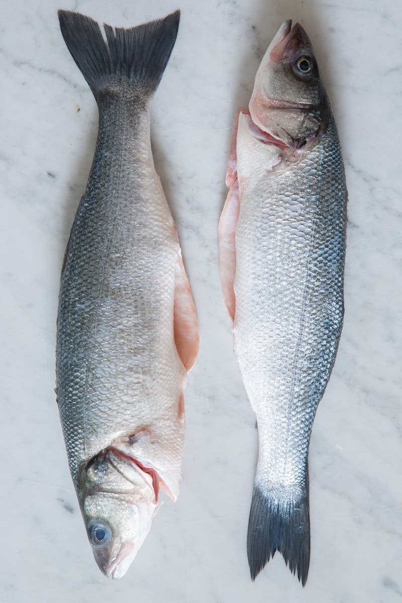 Raw whole branzino on a marble surface.