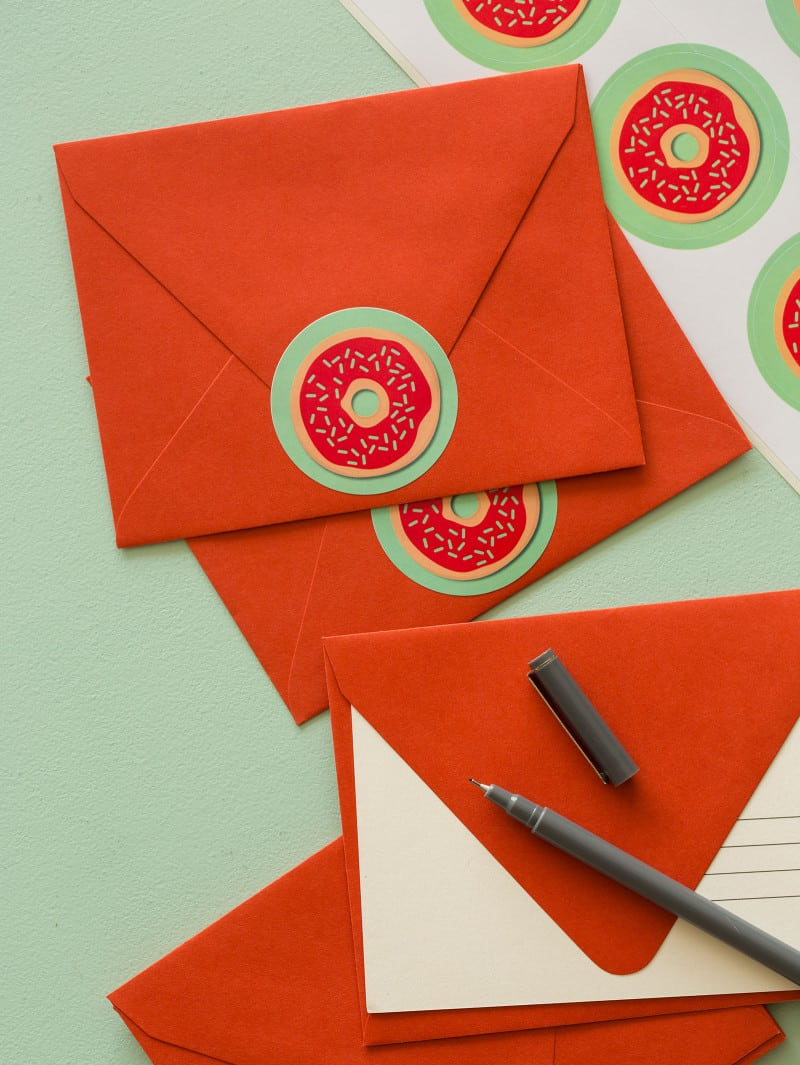 Doughnut printable food gift tags on red envelopes with a pen.