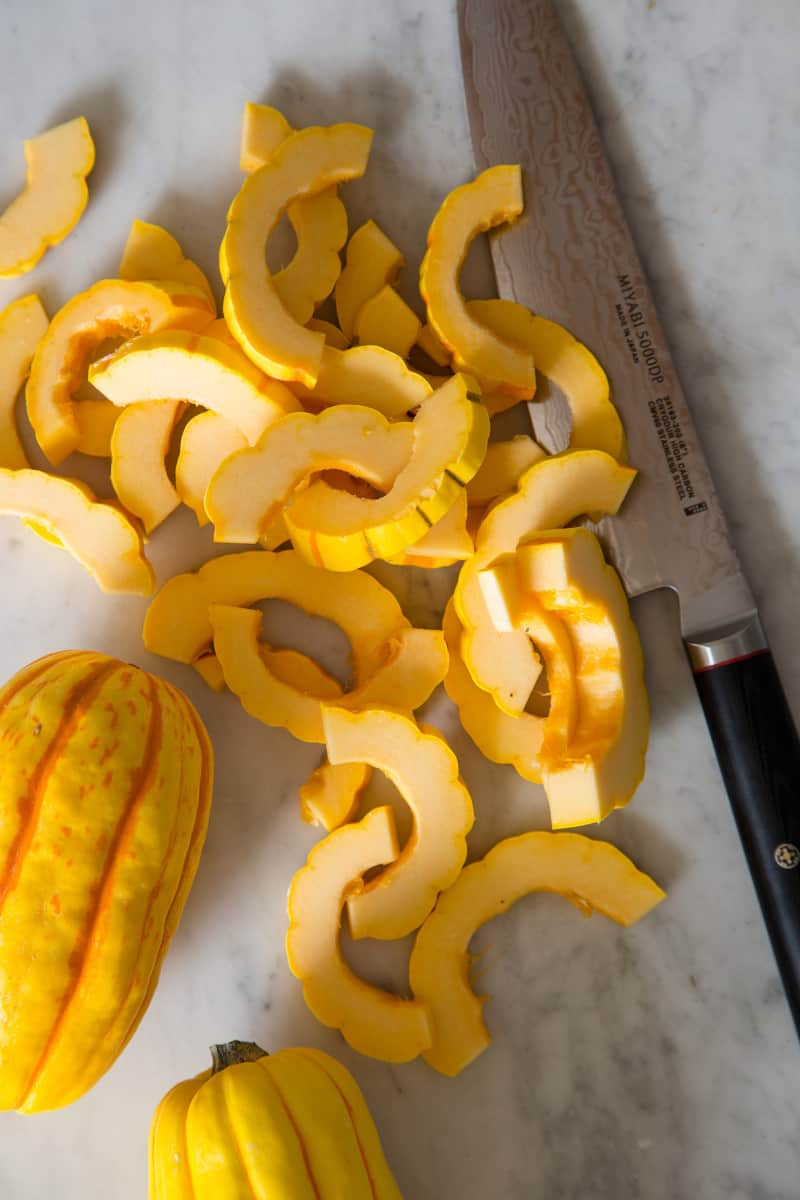 A whole and sliced delicata squash with a knife.