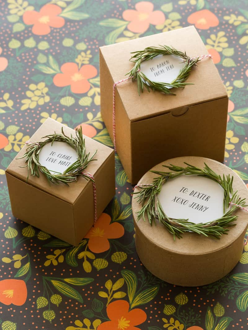 Rosemary wreath gift toppers tied to varying size and shaped brown gift boxes.