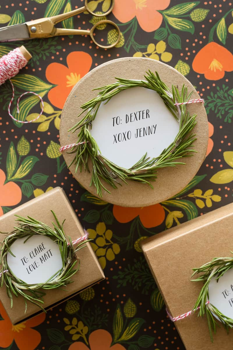 A close up of rosemary wreath gift toppers tied to brown gift boxes.