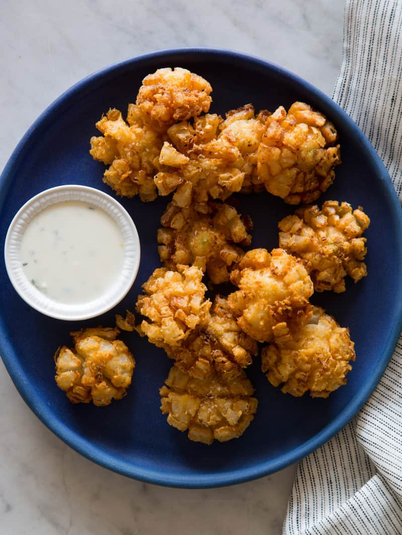 Baby bloomin\' onions on a dark blue plate with a side of buttermilk ranch dipping sauce.