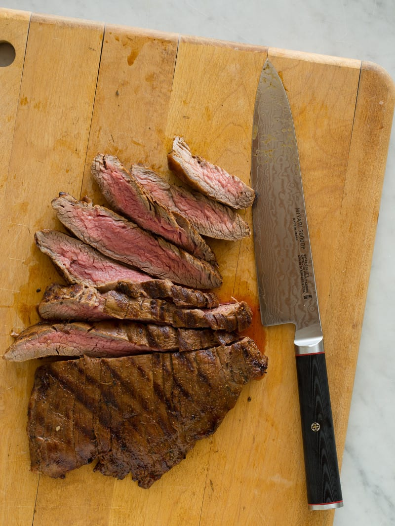 A knife sitting on top of a wooden cutting board with carne asada.