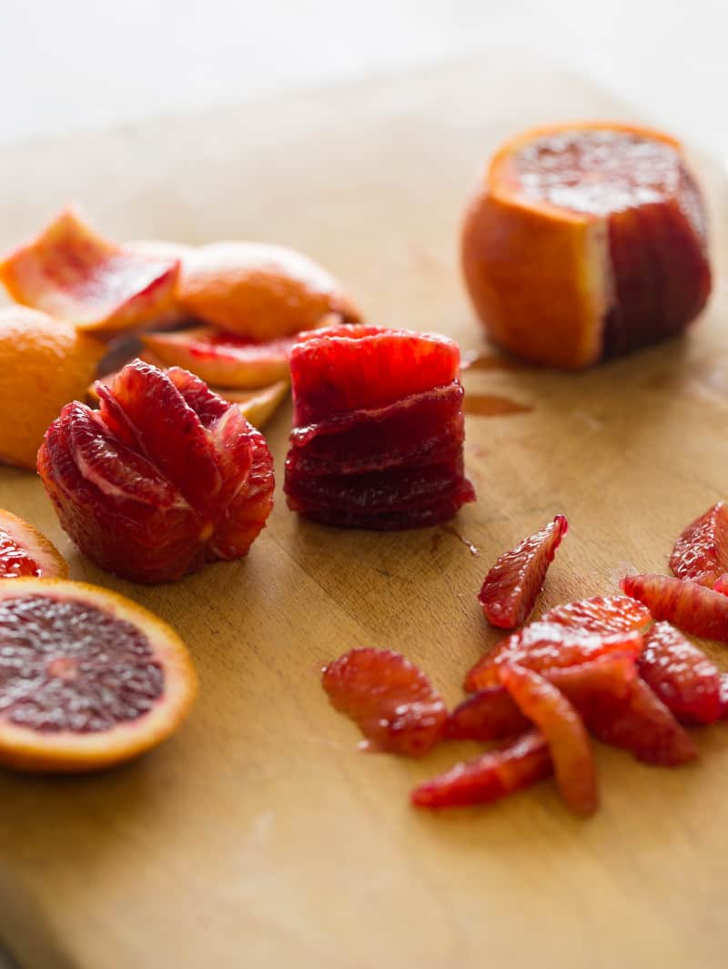 Sliced and segmented blood oranges on a wooden cutting board.