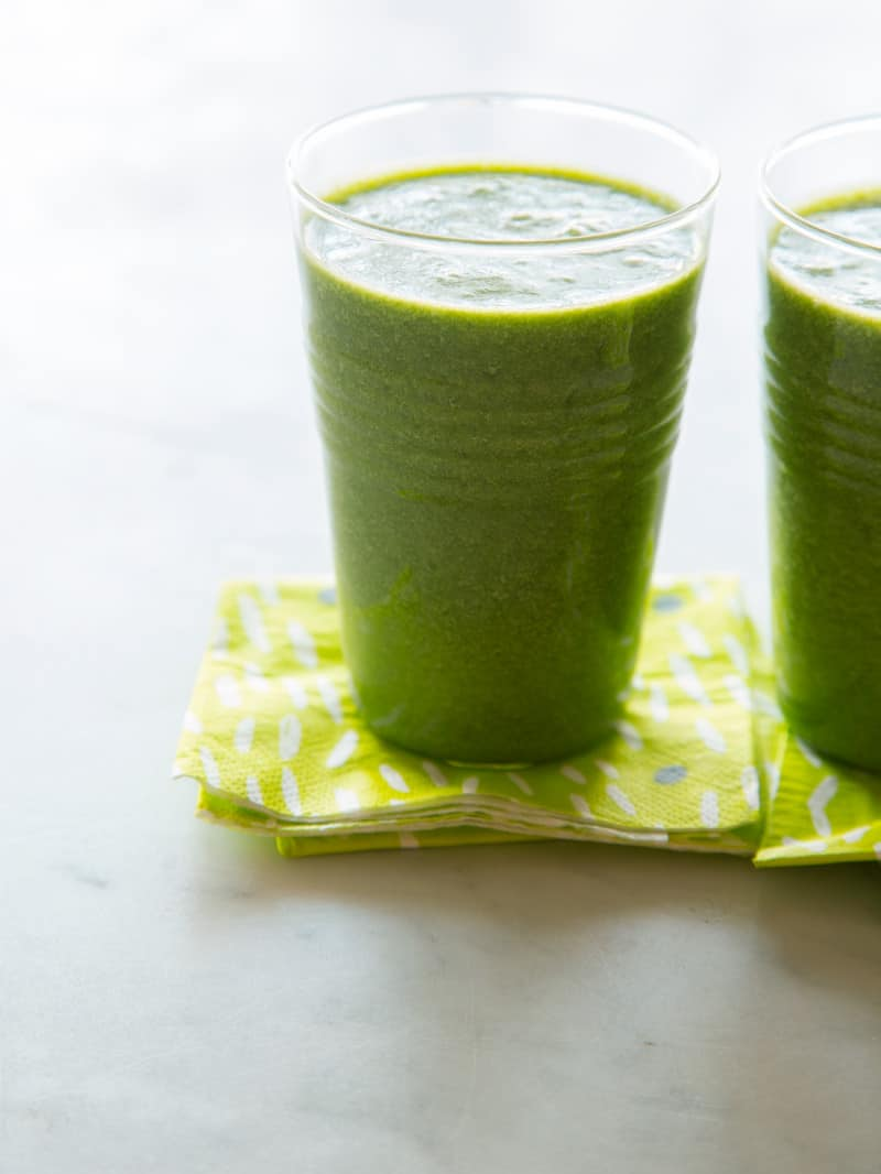 A close up of coconut kale smoothies with green printed paper napkins.