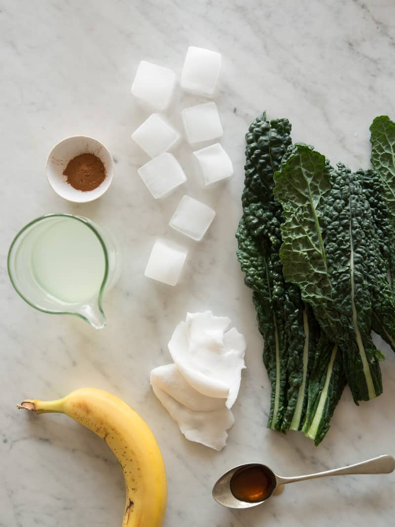 Ingredients for coconut kale smoothies on a marble countertop.