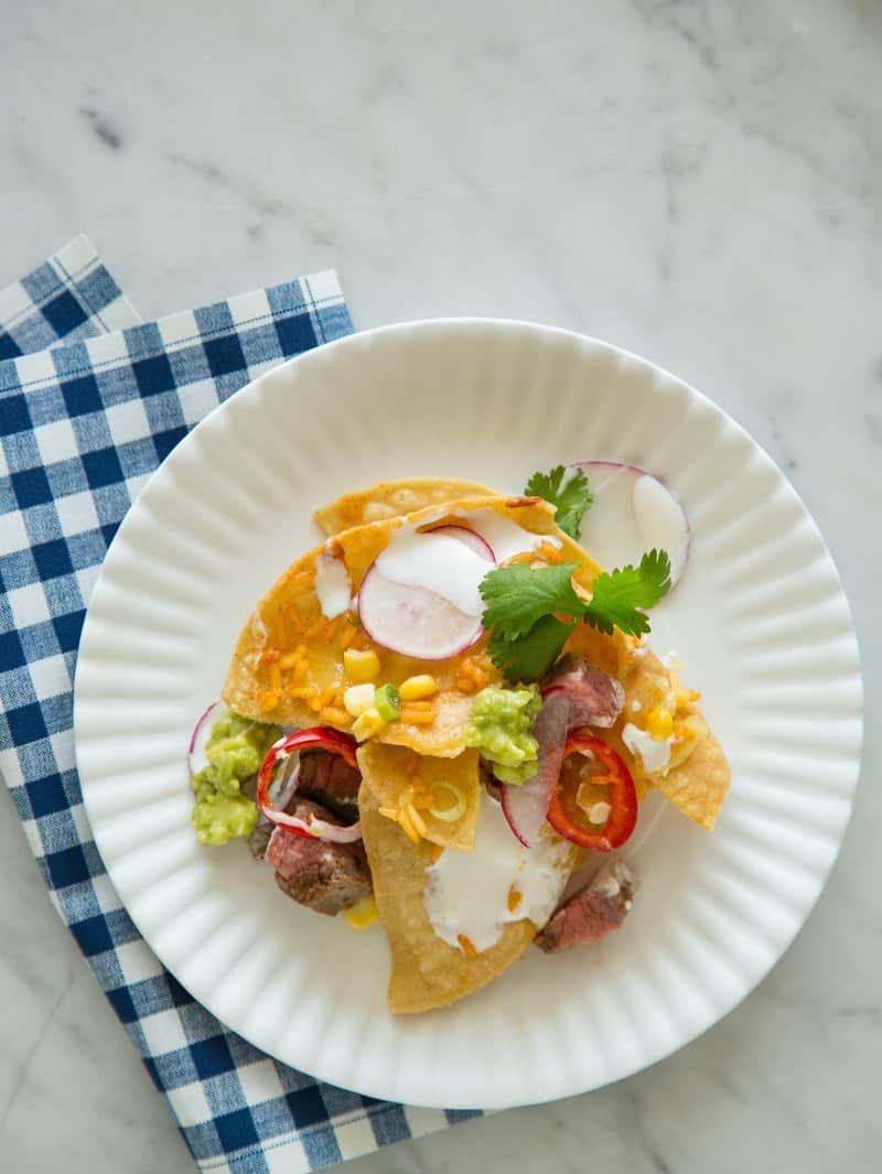 A plate of carne asada nachos with a blue gingham print napkin.