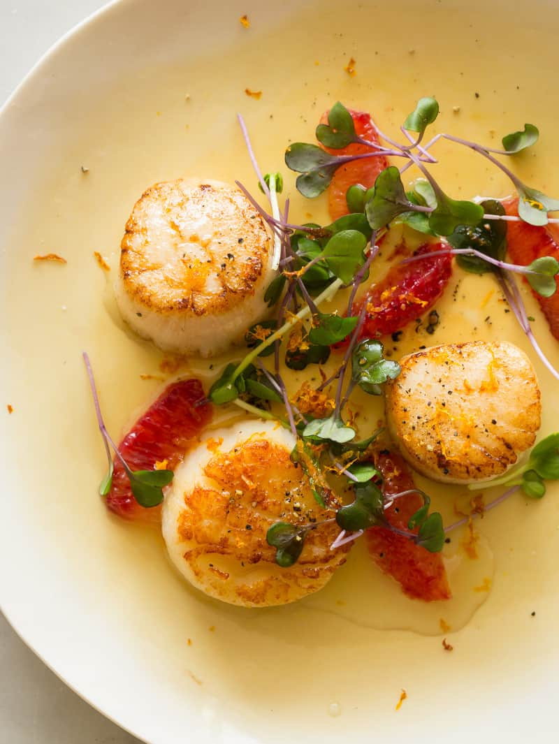 A close up of citrus seared scallops garnished with blood orange segments and micro greens.