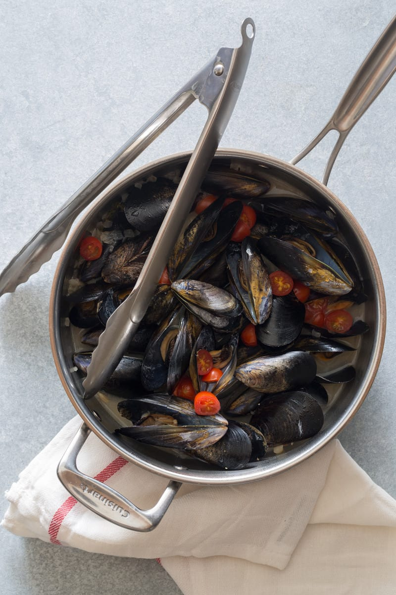 White wine steamed mussels in a pan with cherry tomatoes and tongs.