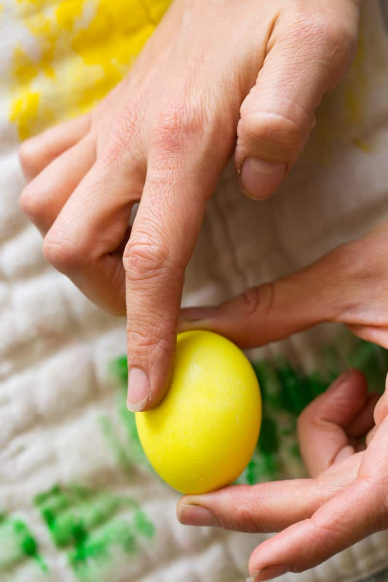 Both hands holding a yellow dyed egg.