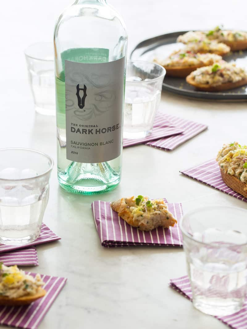 A plate of smoked trout on toast with a wine bottle and glasses with napkins.