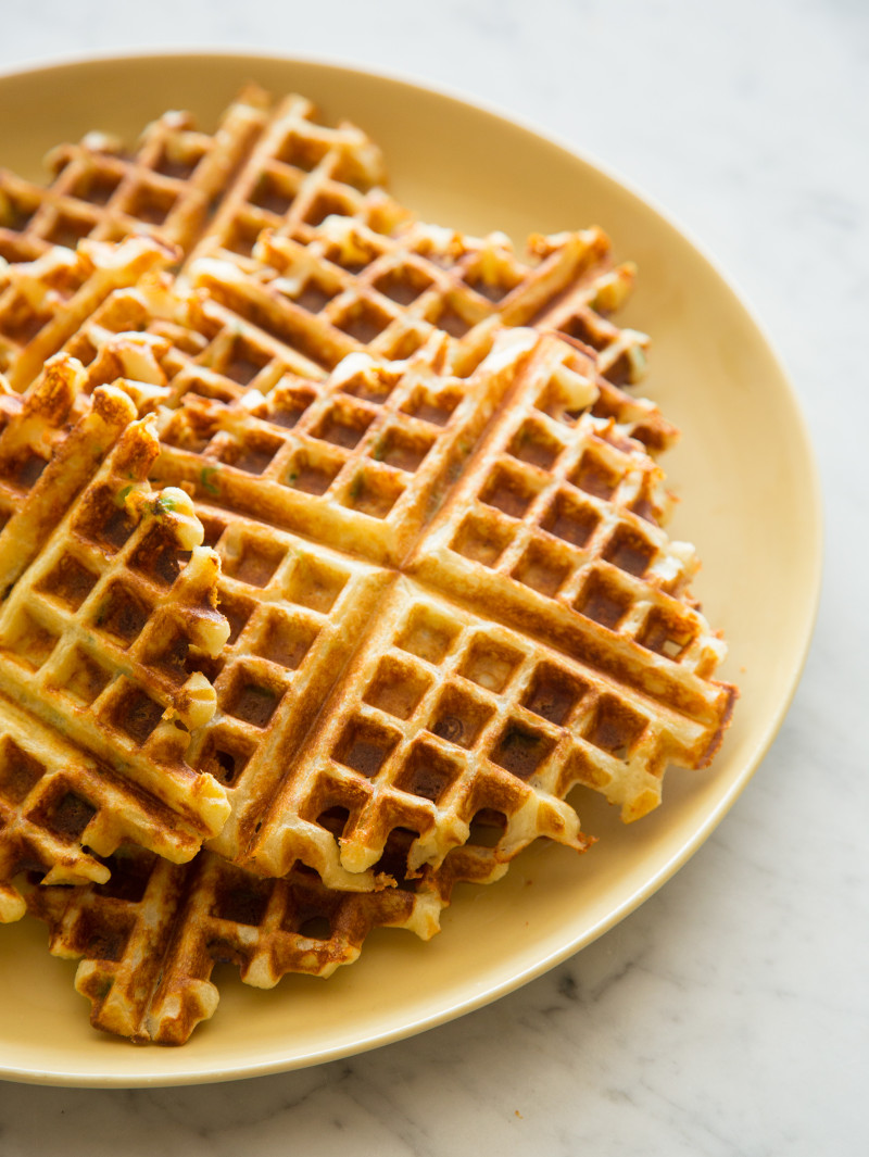 A close up of whole gruyere and green onion waffles on a plate.