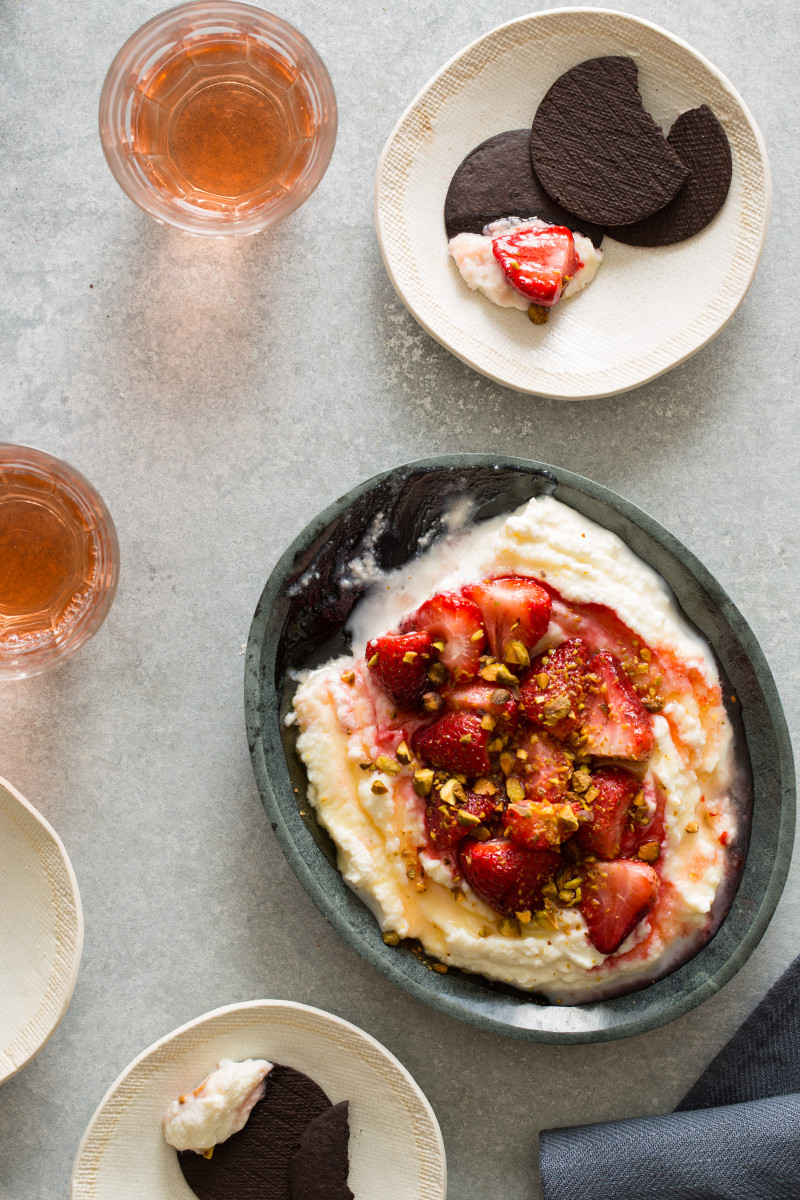 A bowl of roasted strawberries over honey whipped ricotta with a serving on a plate.
