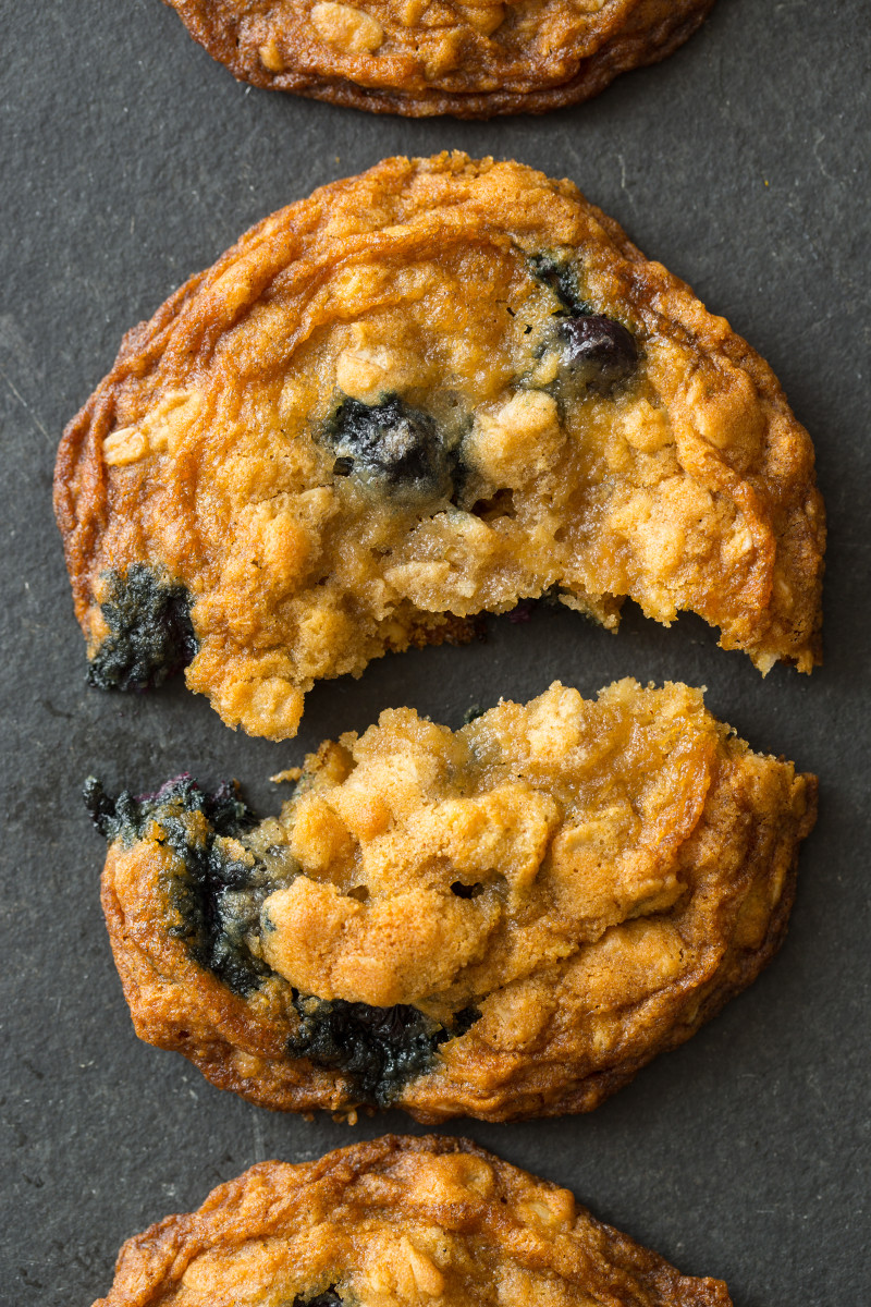 A close up of a blueberry and cardamom oat cookie broken in half.