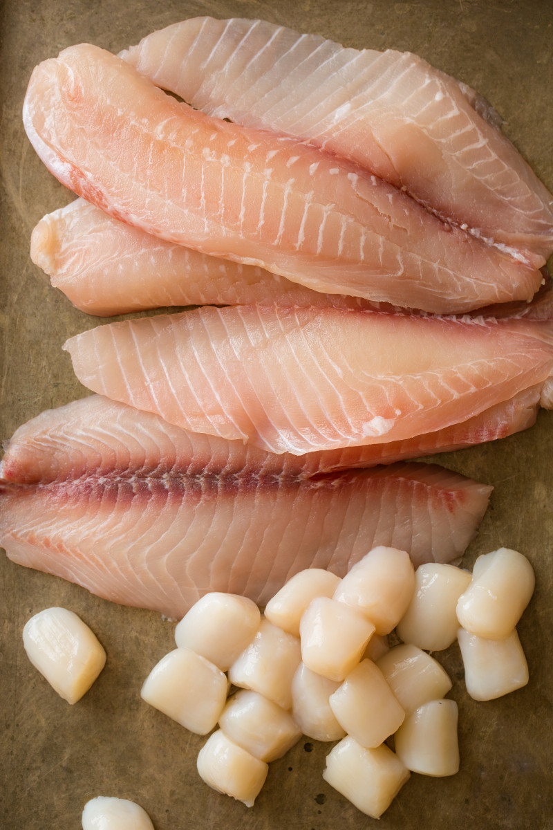 Raw tilapia fillets and bay scallops.