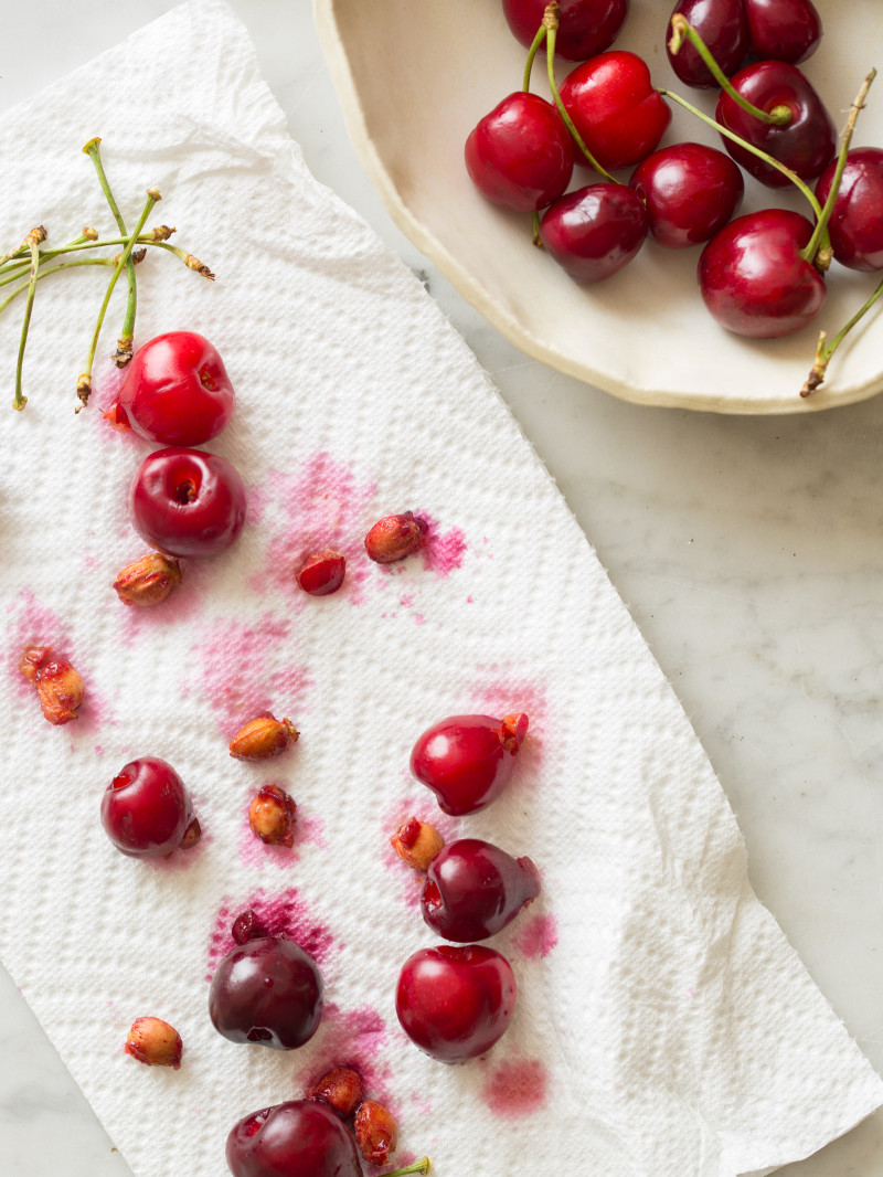 A bowl of fresh cherries next to pitted cherries on a paper towel.