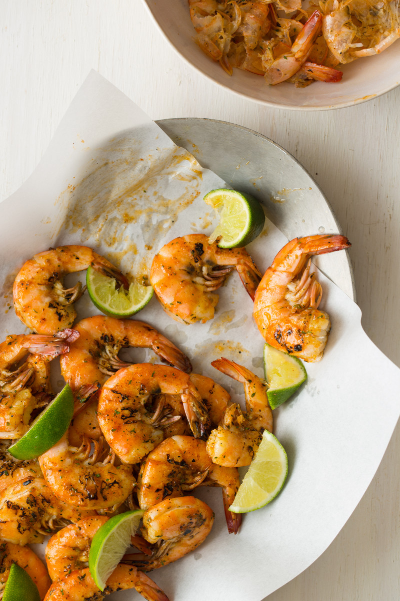 A plate of grilled peel and eat shrimp with lime wedges.