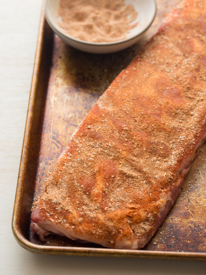 Spare ribs on a baking sheet rubbed with spices.