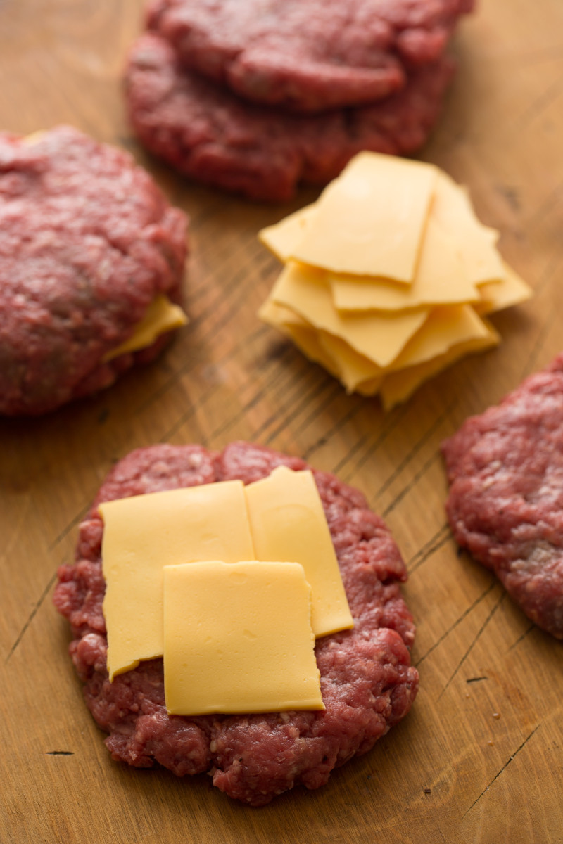 A close up of juicy lucy burger patties with cheese for the stuffing.