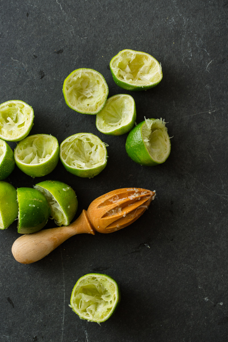 Juiced halved limes with a wooden citrus juicer.