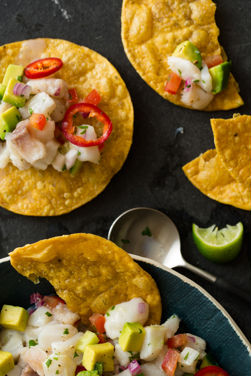 A close up of simple ceviche spooned onto tostadas with lime wedges.