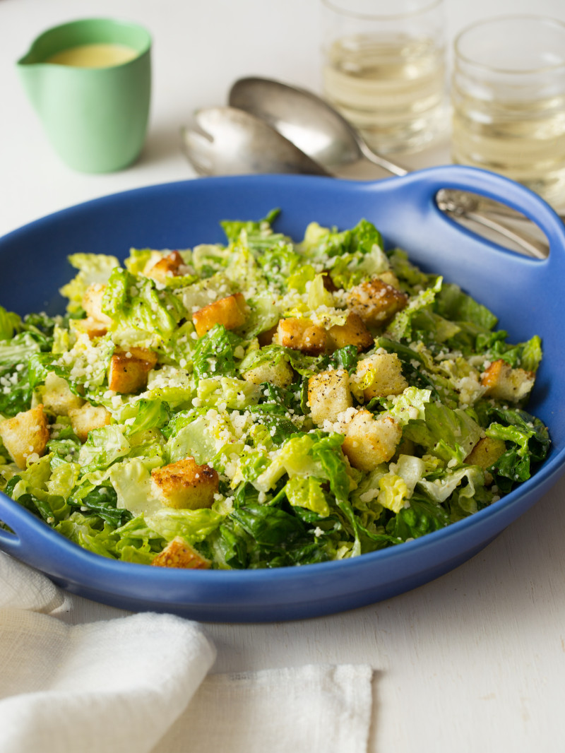 A close up of a large blue bowl of classic caesar salad with tongs and drinks.