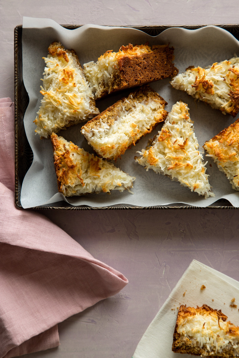 Several triangle cut pieces of coconut oat bars in a pan with pink napkins.