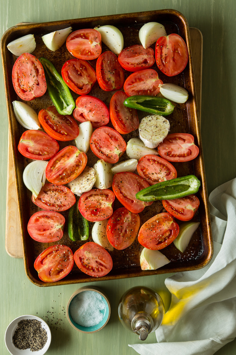 Ingredients for roasted tomato salsa on a baking sheet with salt and pepper on top.
