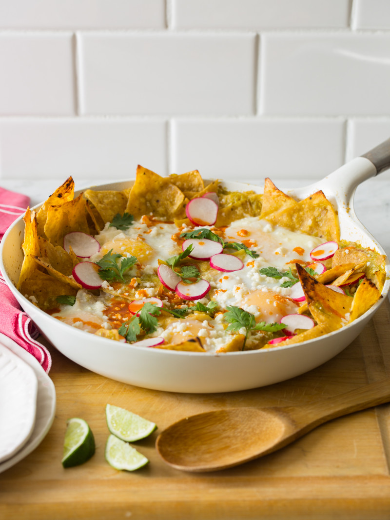 Green chilaquiles in a pan on a wooden surface with a wooden spoon.