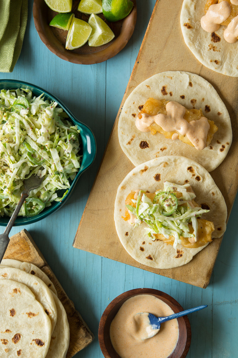 Baja fish tacos being assembled on a wooden cutting board.