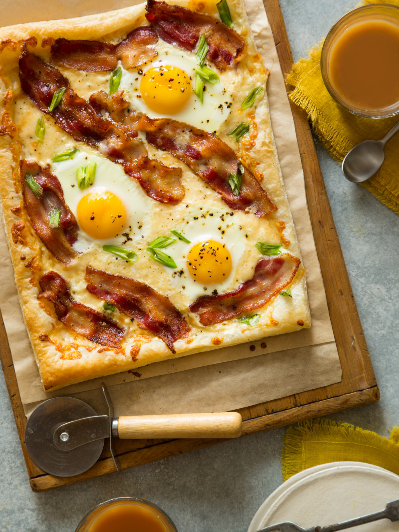 A breakfast tart on parchment paper and a wooden cutting board with a pizza cutter.