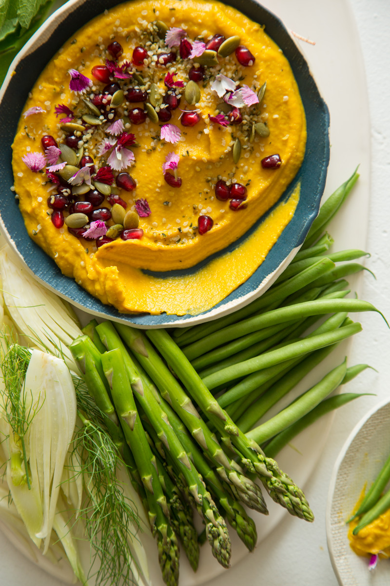 A close up of a bowl of roasted pumpkin hummus with a variety of veggies.
