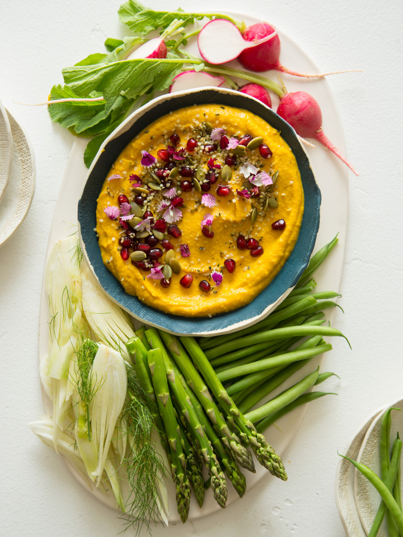 A bowl of roasted pumpkin hummus on a platter with a variety of veggies.