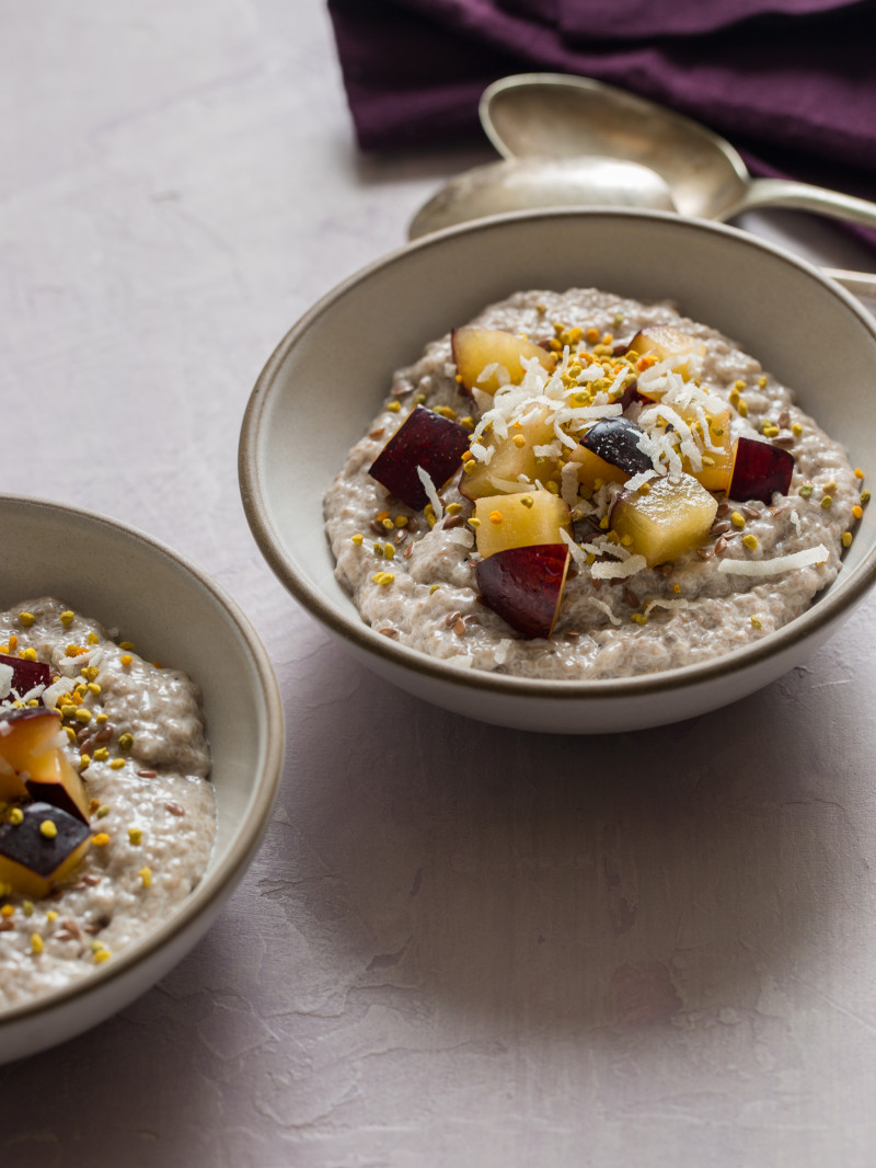 A close up of chia seed pudding topped with fruit and shredded coconut in a bowl.