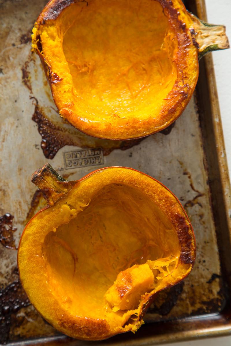 Roasted halved pumpkins on a sheet pan.