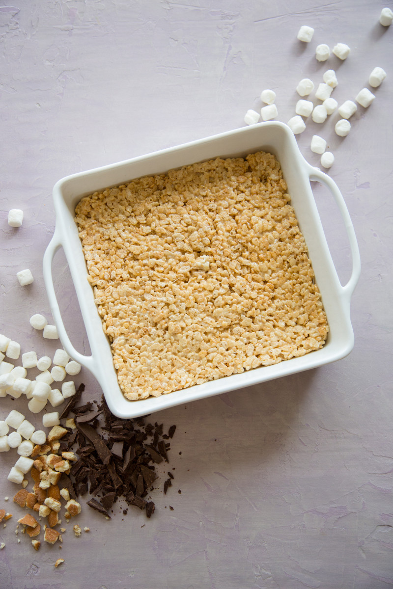 A white baking pan of rice krispies treats layer for s\'mores rice krispies treats.