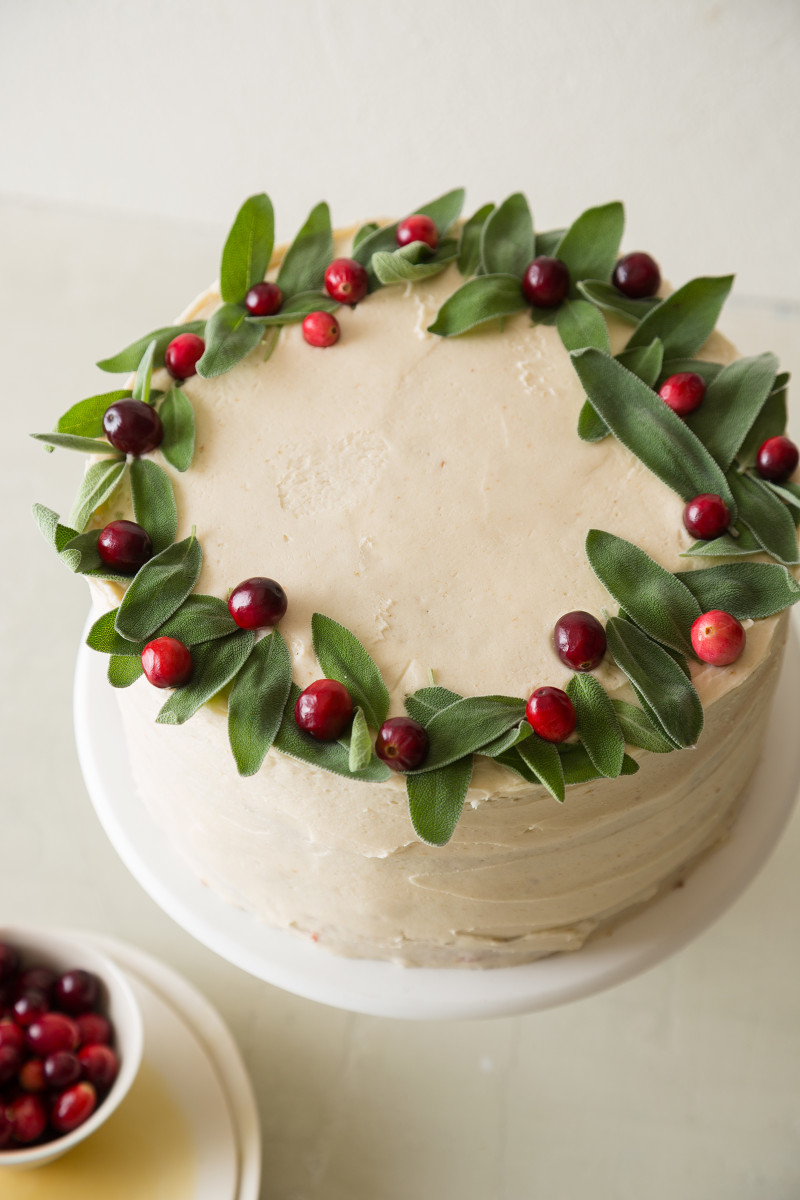 The top of an apple cranberry cake decorated with fresh cranberries and sage.